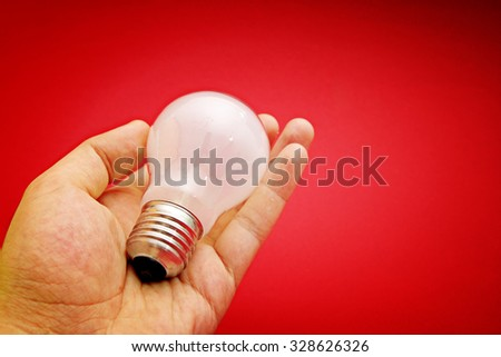 Background with lit lightbulb. Isolated on red - stock photo