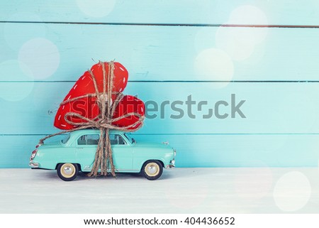 Background with miniature blue toy car carrying a heart on blue painted wooden planks. Place for text. - stock photo