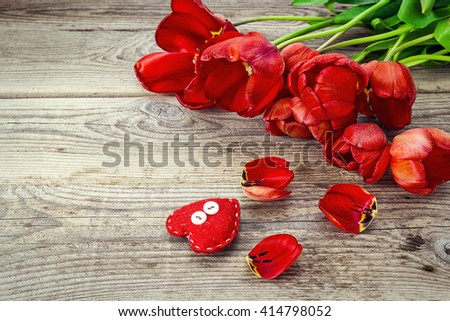 Background with red tulips and heart on grunge wooden boards. Place for text. - stock photo