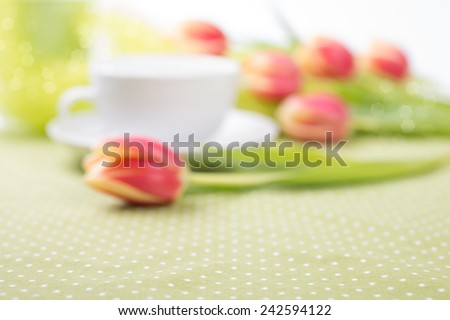 Background with red tulips on the table and white tea cup out of focus, space for your text - stock photo