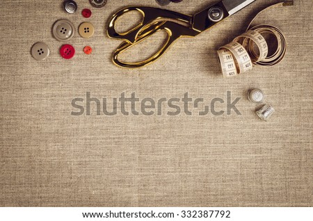 Background with sewing and knitting tools and accesories. Set for needlework placed on flax fabric. Image taken from above, top view. A lot of copyspace. - stock photo