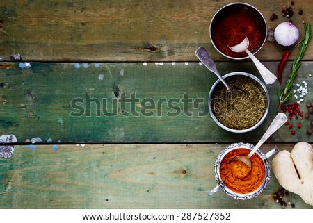 Background with Spices. Herbs and spices selection - old metal cups and rustic wooden board. Cooking, food or health concept. Space for text - stock photo
