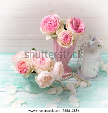 Background with sweet pink roses  on turquoise painted wooden planks against white wall. Shabby chic.  Selective focus. Square image.