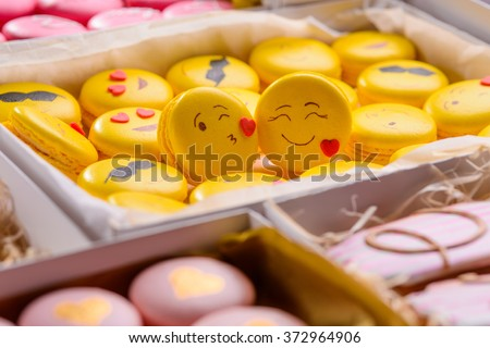 Background with sweets in boxes and two yellow macaroon with smiles close-up. The foreground is blurred. A gift on Valentine's Day. - stock photo