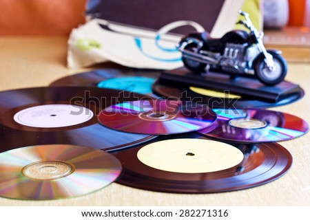 Background with Vinyl record discs ans CD, bike. Focus on foreground. Image with blurred background - stock photo