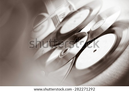 Background with Vinyl record discs ans CD. Focus on foreground. Black and white image with view through CD hole - stock photo