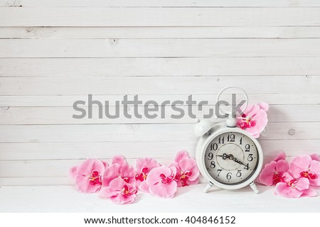 Background with white alarm clock and flowers pink orchid on white painted wooden planks. Place for text.  - stock photo