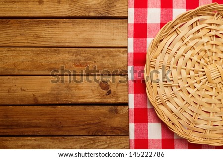 Background with wooden deck board, checked tablecloth and wicker plate - stock photo