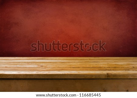Background with wooden table and red grunge wall