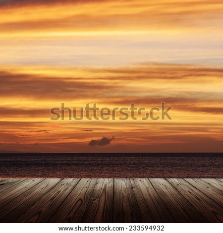 Background with wooden table and sunset over the sea - stock photo