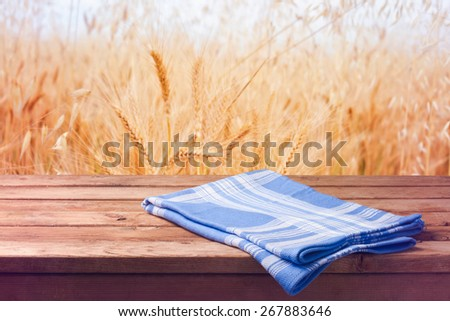 Background with wooden table and wheat field - stock photo
