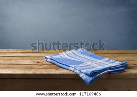 Background with wooden table, tablecloth and grunge blue wall - stock photo