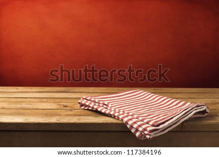 Background with wooden table, tablecloth and  grunge red wall - stock photo