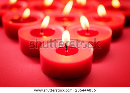 Backgrounds and textures: close-up shot of burning red candles, selective focus, holiday or celebration background - stock photo