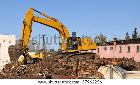 Backhoe Demolishes Old Buildings in Preparation for new Road and Bridge - stock photo