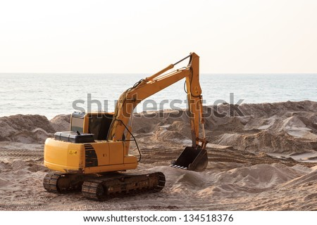 Backhoe digging in the sand to protect the coast - stock photo