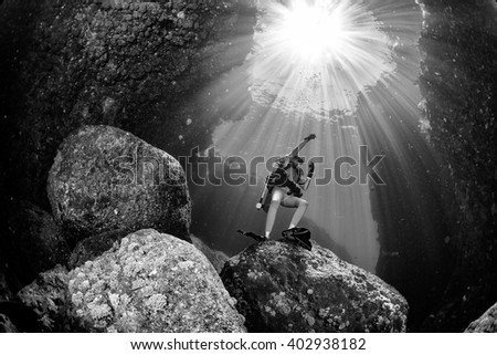 backlight diver underwater coming to the deep ocean - stock photo