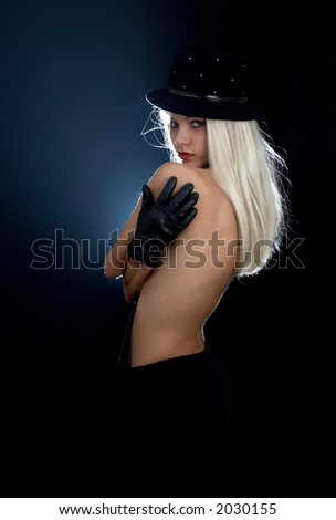 backlight image of cabaret girl in hat and tie