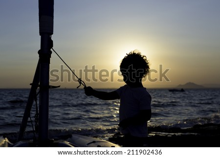 backlight of a kid playing with a boat on the beach - stock photo
