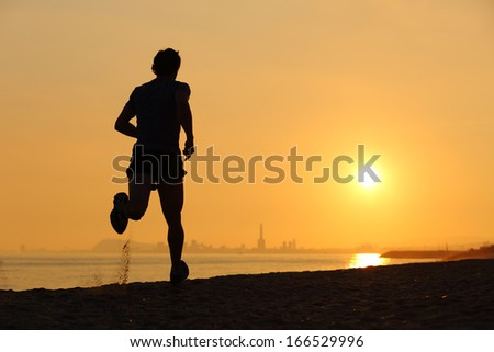 Backlight of a man running on the beach at sunset with the horizon in the background - stock photo