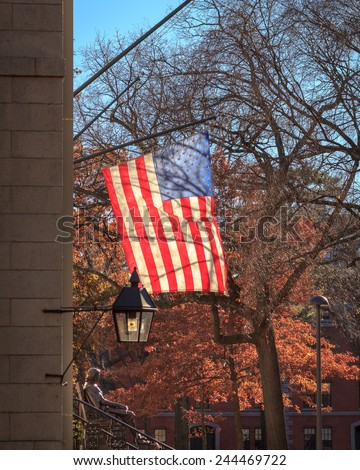 Backlit american flag over the John Harvard statue on a beautiful fall day in Cambridge, MA, USA. - stock photo