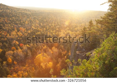Backlit cliff and pines with lens flare above aspen trees in Fall color on Oberg Mountain in northern Minnesota - stock photo
