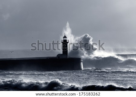 Backlit dramatic big wave over lighthouse. Toned blue. - stock photo