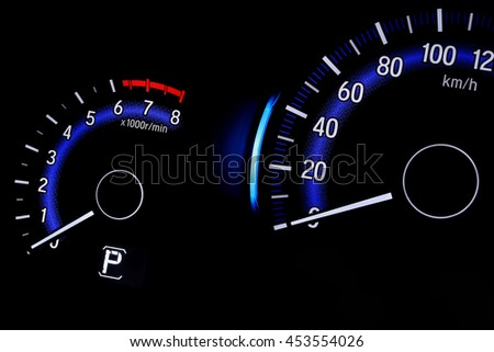 Backlit gauges of an automobile. Blue glowing meters speedometer isolated on black background.