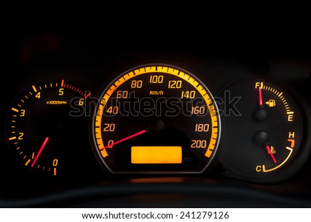 Backlit gauges of an automobile. Yellow glowing meters with a red needle. Fuel, tachometer, and speedometer. Isolated against black background. - stock photo