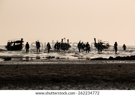 Backlit group of people walking in shallow water with dramatic lighting at a beach with wooden long-tail boats - stock photo