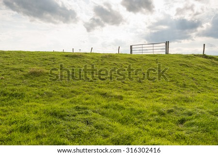 Backlit image of the grassy slope of an embankment with a fence of barbed wire and a steel gate on top of the embankment seen from the base of the dike. - stock photo