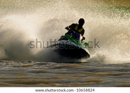 Backlit jet ski with water spray - stock photo