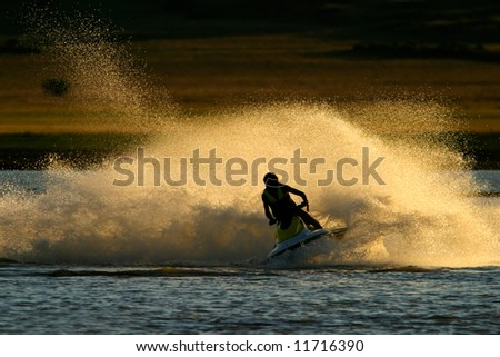 Backlit jet ski with water spray, late afternoon - stock photo