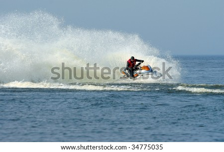 Backlit jet ski with water spray on the blue sea. Jetski in action, man on a jet-ski, making splashes. - stock photo