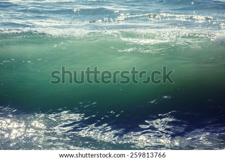 Backlit ocean wave about to break. Abstract background. - stock photo