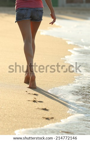 Backlit of a woman legs walking on the sand of the beach seashore leaving footprints                - stock photo