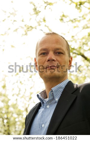 Backlit portrait of a friendly business man. A happy average guy, dressed smart casual, seen from a low point of view, looking ito the camera - stock photo