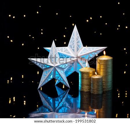 Backlit stars in blue with golden candles in front of dark background - stock photo