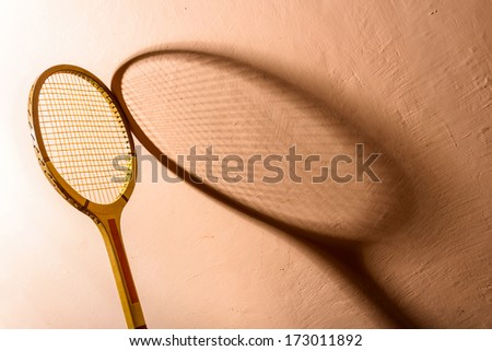 Backlit vintage tennis racket and its shadow on a pink background - stock photo