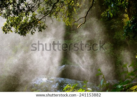 Backlit water spray from a waterfall in a forest - stock photo