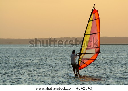 Backlit windsurfer at sunset on calm coastal water	 - stock photo