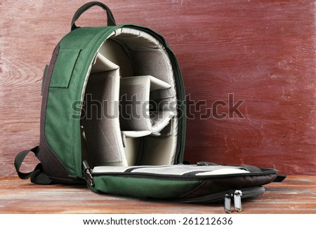 Backpack for camera on wooden background - stock photo