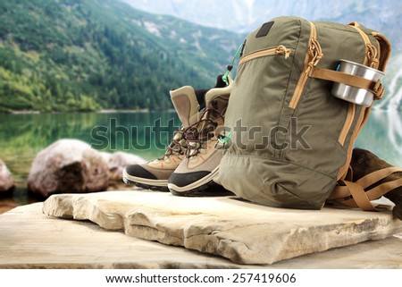 backpack on rock and stones in lake  - stock photo