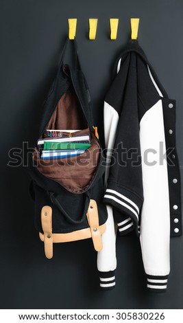 Backpack with books weighs on the wall next to the bomber