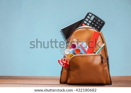 Backpack with clerical accessories, blue background - stock photo