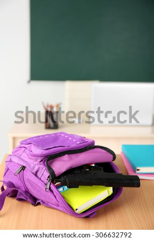 Backpack with gun in classroom, close up. Juvenile delinquency - stock photo