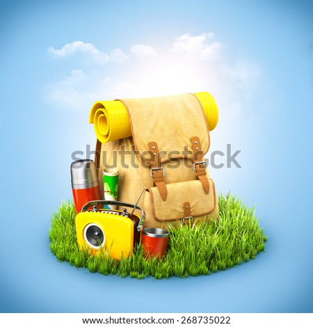 Backpack with termos, map and radio on grass at blue background. Unusual travel background - stock photo