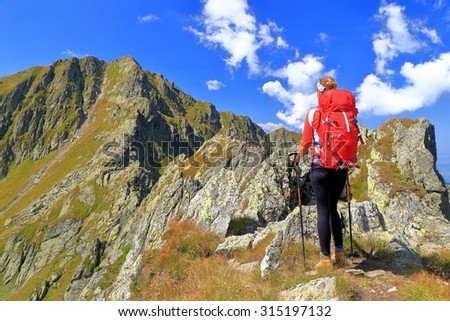 Backpack woman admires distant summits in sunny day