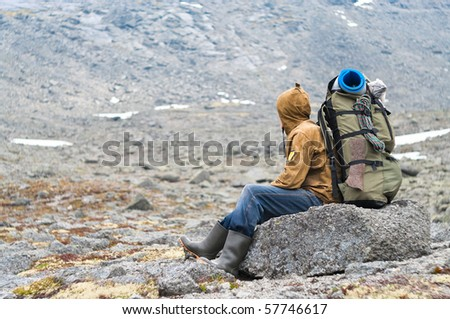 Backpacker a senior man sitting on rock in mountains - stock photo