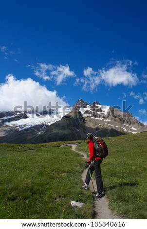 Backpacker admiring the view on the Tour of Mont Blanc, France - stock photo